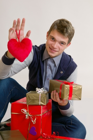 Valentines Man /  Teenager holding heart and gifts isolated on white background Stock Photo - 17370202