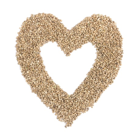 Hemp seeds in heart shape on white background