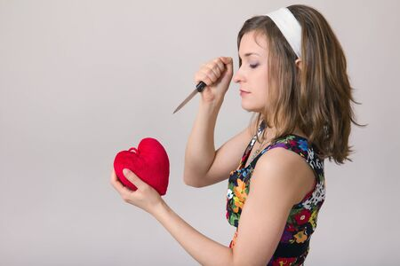 Pretty pin up woman cutting a heart  toy with a kitchen knife photo