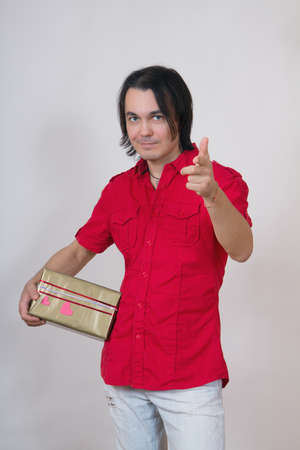 Beautiful young Valentines Man holding a gift and pointing on camera Stock Photo - 17370193
