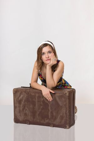 Beautiful girl in pin up style leaning on old suitcase photo