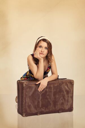 Beautiful girl in pin up style leaning on old suitcase, toned in retro style photo