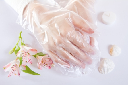 White protective transparent single use gloves with flowers. Top view