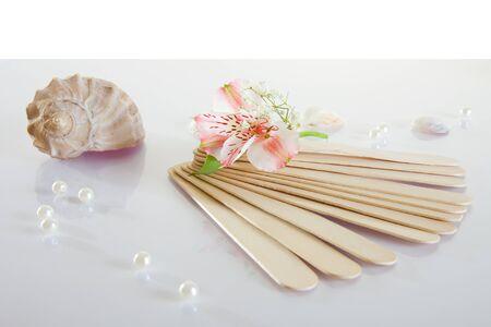 Wooden medical tongue depressors on white background photo
