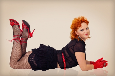 Pretty girl with red hairs lying on the floor