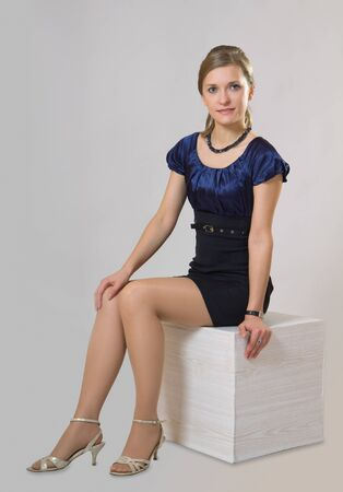 Beautiful slim woman with blond hair in classical silk dress Stock Photo