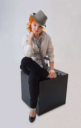 Young woman with red hair and hat sitting on black cube photo