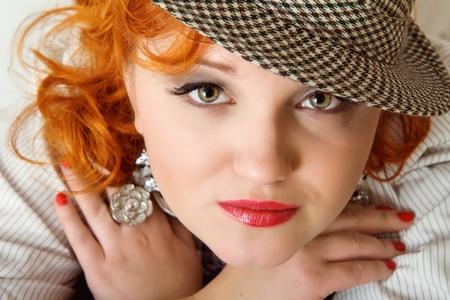 beautiful young woman with red curly hairs wearing fedora hat photo