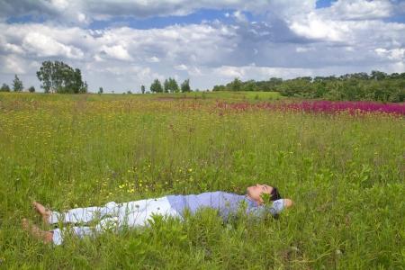 so�ando: Feliz joven tumbado en la hierba con hermosas flores silvestres en un d�a soleado