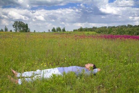 Happy young man lying on grass with beautiful wildflowers at sunny day Stock Photo