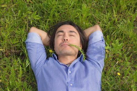 Happy young man lying on grass at sunny day photo