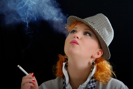 Attractive woman with red hairs in a felt hat smoking a cigarette photo