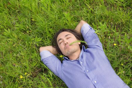 Close up of young handsome business man relaxing outdoor lying on back on green grass photo