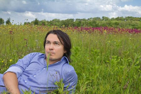 Happy young man lying on a spring meadow with beautiful wildflowers photo