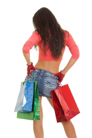 Slim woman standing with shopping bags isolated on a white photo