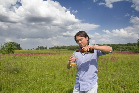 Happy young man pouring glass of beer from bottle on a spring meadow photo