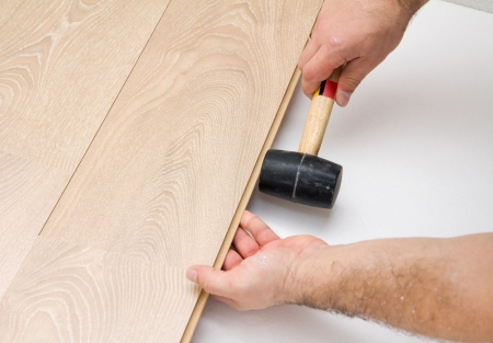 carpenter worker installing laminate floor during flooring work with hammer