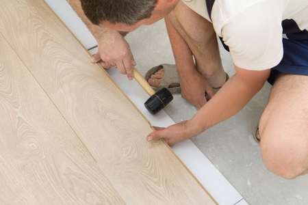 Two carpenter workers installing laminate board during flooring work with hammer