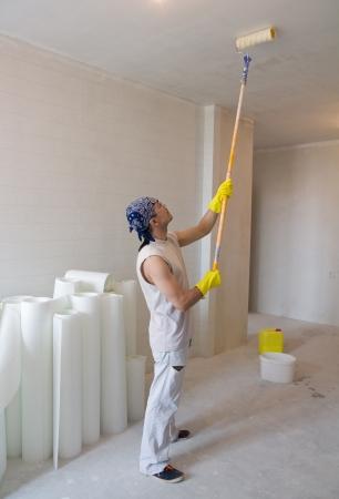 pintor de casas: Hombre joven - Casa pintor pintura del techo trabajador con el rodillo de pintura