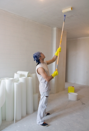 Young man - house painter worker painting ceiling with painting roller photo