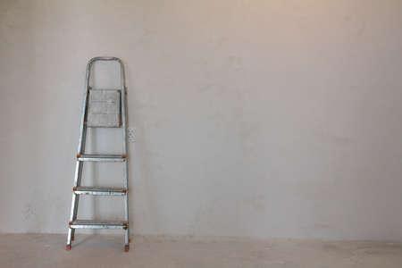 home improvement: dirty ladder near the wall