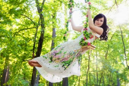 Beautiful woman swinging on flower swing in summer forest