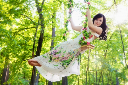 Beautiful woman swinging on flower swing in summer forest