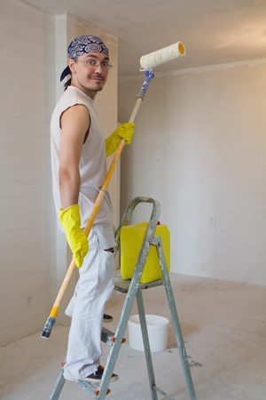 Young man painting ceiling with painting roller photo