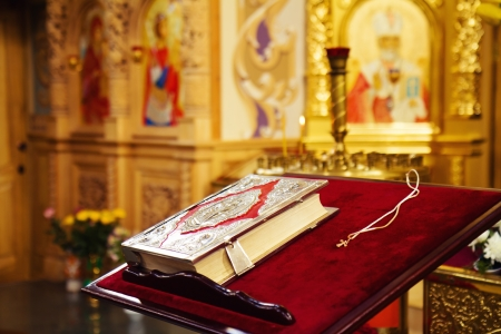 iconostasis: Holy Bible and Orthodox cross prepared for christening ceremony in russian church