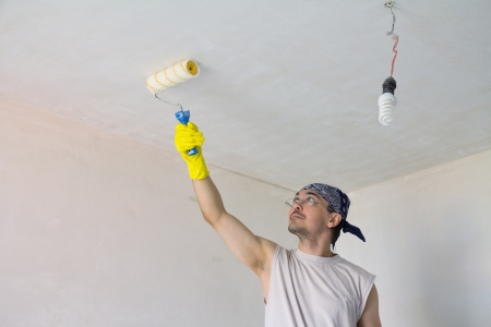 Young worker painting ceiling with painting roller photo