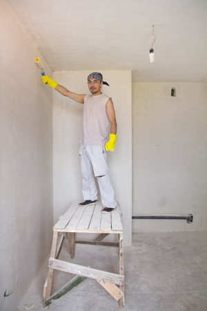 Young man painting wall with painting roller photo