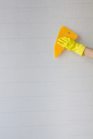 Workers hand in yellow protective gloves with spatula smoothing wallpaper  photo