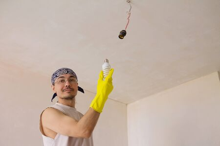 Close up of electrician wiring a ceiling light photo