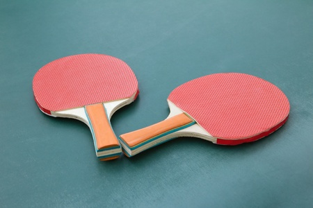 Red table tennis ping pong two paddles on green board photo