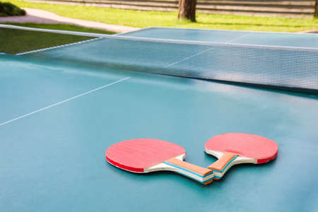 Two red table tennis ping pong racket on green board photo