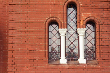 Stained Glass Window in church and red brick wall photo