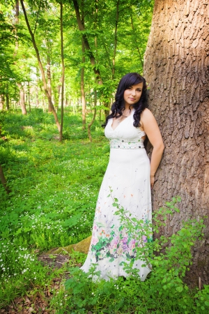 Enjoying the nature. Beautiful young woman wearing elegant white dress standing near tree in summer forest photo