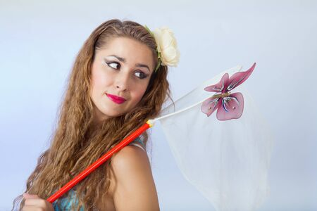 Young female in pin-up style holding a butterfly net and looking at a butterfly on blue background photo