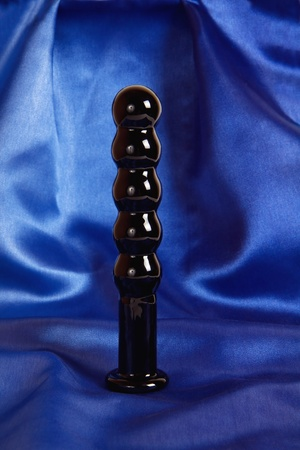 black sex: Black sex anal toy - butt plug made of glass on blue background