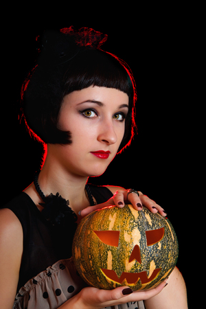 Beautiful Halloween woman in retro style with pumpkin in her hands photo