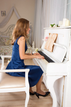 beautiful young woman in blue playing the white piano photo