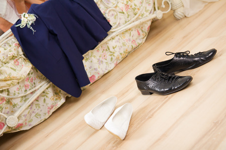 Huwelijksnacht. Ontkleed trouwkleding, pak en schoenen in de buurt van een bed