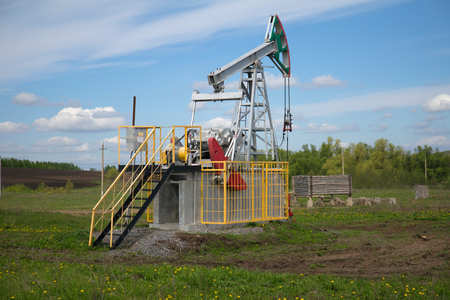 oilwell: oil pump jack with a green field in background