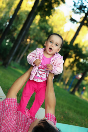 Cute toddler girl and her father playing in the park photo
