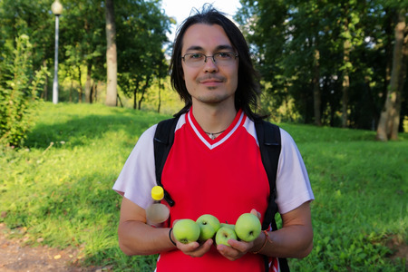 Handsome man with green apples in garden photo