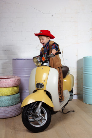 Young boy dressed as a cowboy riding the motorbike. Studio photo