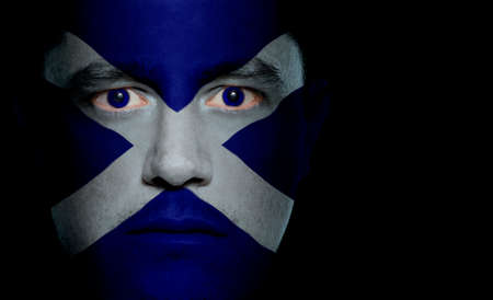 aggressor: Scottish flag paintedprojected onto a mans face. Stock Photo