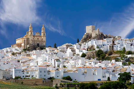 Olvera is a white village (pueblo blanco) in Cadiz province, Andalucia, Spain.  It features a moorish fortress and a neoclassic cathedral overlooking the whitewashed village. Stock Photo