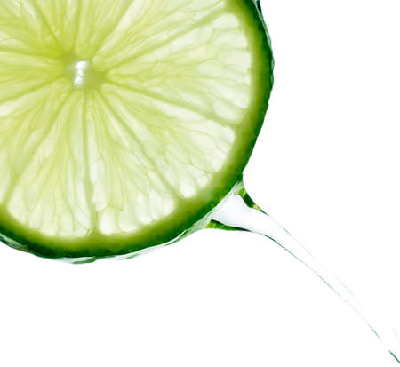 Crystal clear water splashing from a slice of lime.  Isolated on a white background.