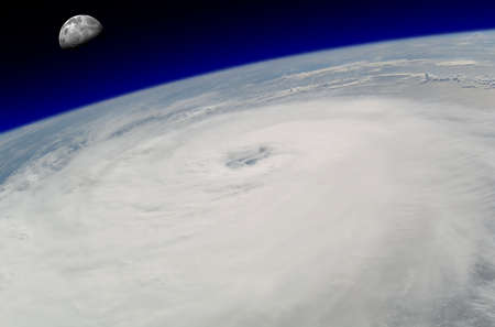 View from space of a giant hurricane over the ocean with moon in background.